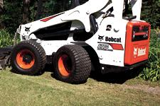 Bobcat A770 all-wheel steer loader and mower attachment maintaining a lawn