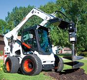 Bobcat A770 all-wheel steer loader with auger attachment digs a hole.