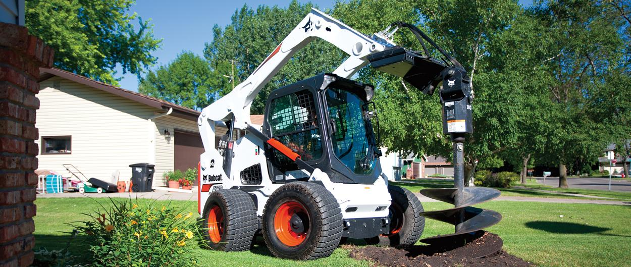Bobcat A770 all-wheel steer loader digs hole with auger attachment.