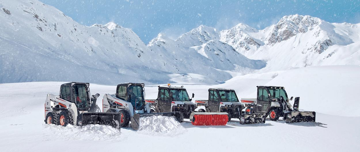 Bobcat loaders, utility vehicles and a Toolcat utility work machine equipped with snow-removal attachments push into a snowy field in a mountainous landscape.
