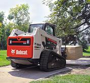 Bobcat T630 compact track loader hauls load on pallet fork attachment.