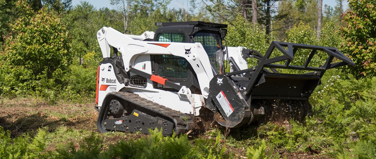 Bobcat T870 compact track loader clears brush with the forestry cutter attachment.