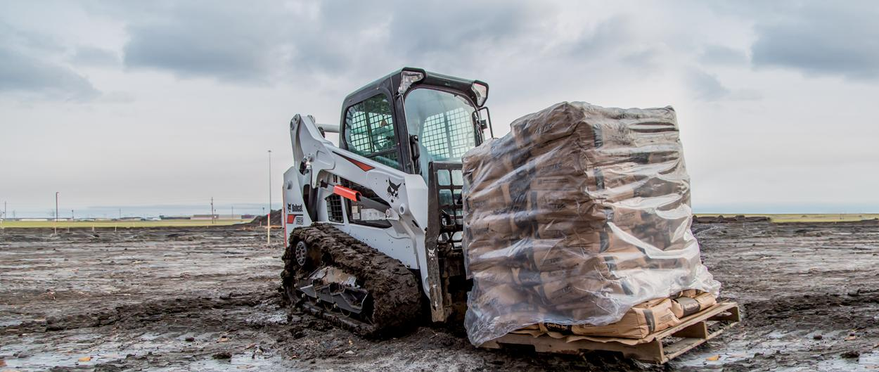 Bobcat T590 compact track loader hauling material with the pallet fork attachment.