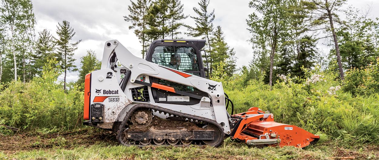 Bobcat T595 compact track loader lifts bags of building material with pallet fork.