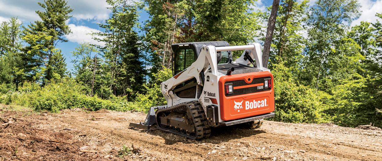 Bobcat T595 compact track loader clearing brush with landplane attachment.