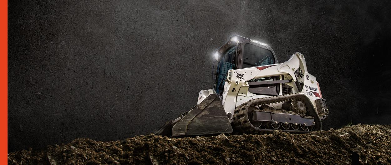 Bobcat M2-Series T595 compact track loader and a bucket attachment uses lights to work in the dark.