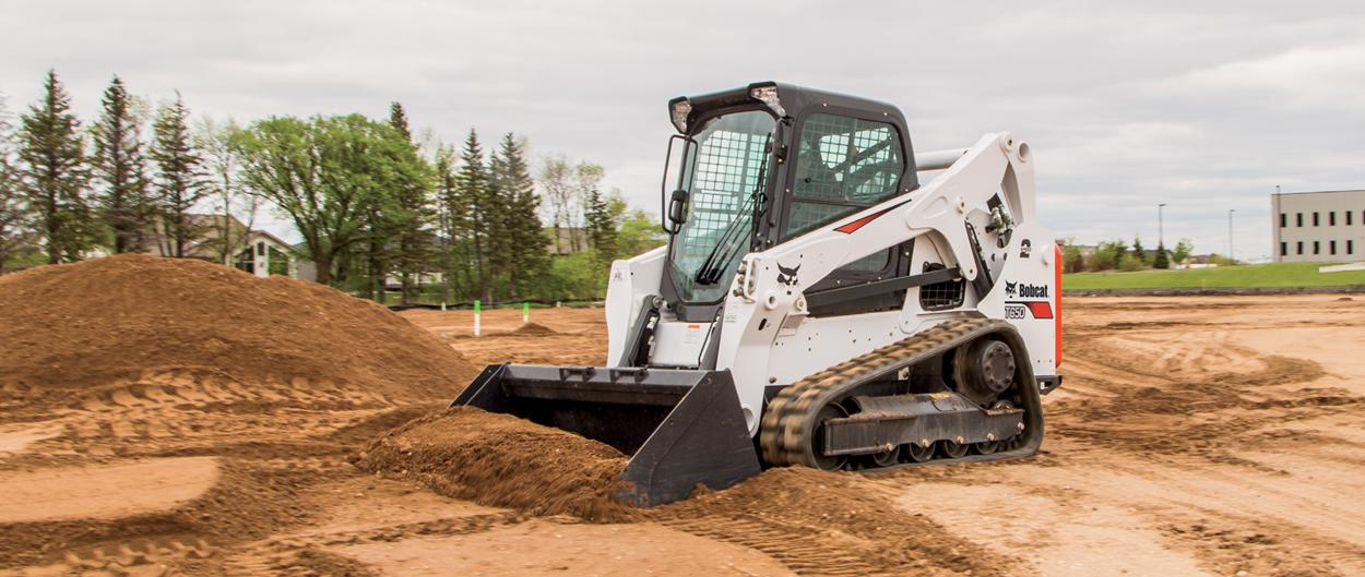 Bobcat T650 compact track loader and bucket attachment scoops up dirt.