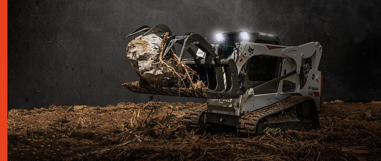 Bobcat M2-Series T770 compact track loader and a grapple attachment uses lights to work in the dark.