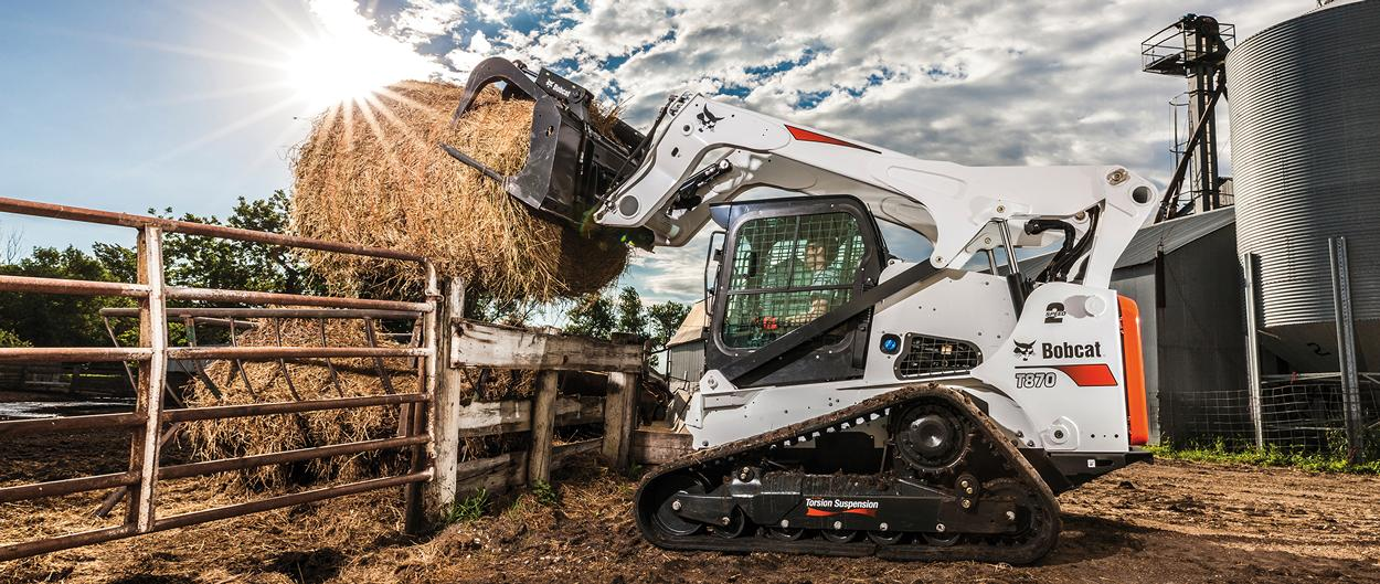 Bobcat T870 compact track loader and industrial grapple attachment moving a round hay bale into a feeder.
