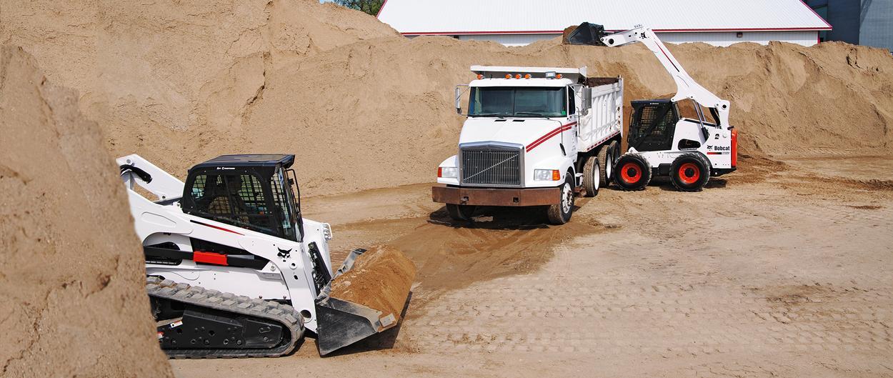 Bobcat skid-steer loader and compact track loader load truck.