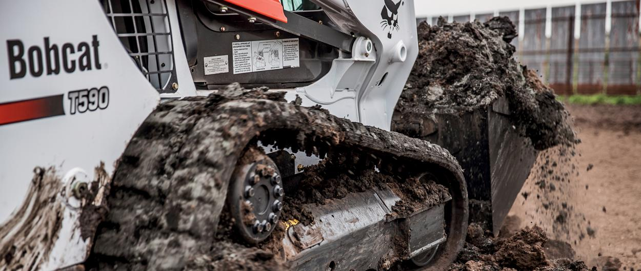 Close-up view of the new undercarriage system from Bobcat on a T590 compact track loader as it travels in muddy ground.