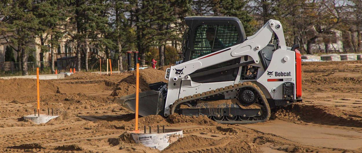 Bobcat T595 compact track loader grades fill at a construction site.