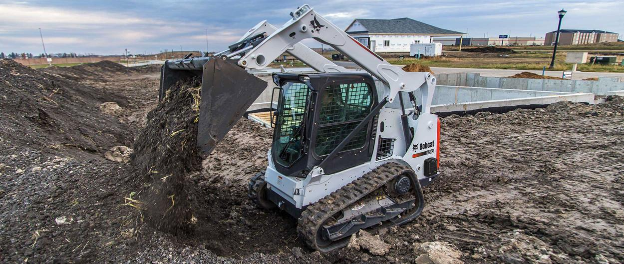 Bobcat T595 compact track loader unloads bucket of black dirt at a construction site.