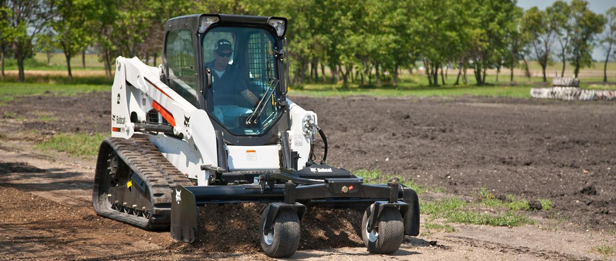 Bobcat T630 compact track loader levels dirt using the box blade attachment.