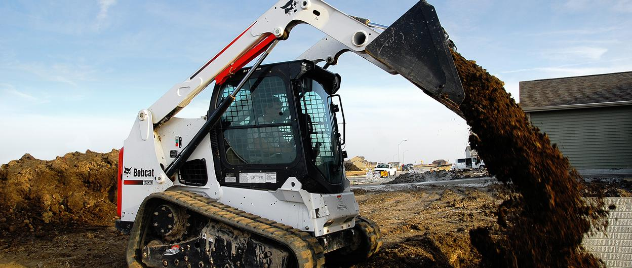 Bobcat T630 compact track loader empties a bucket of manure.