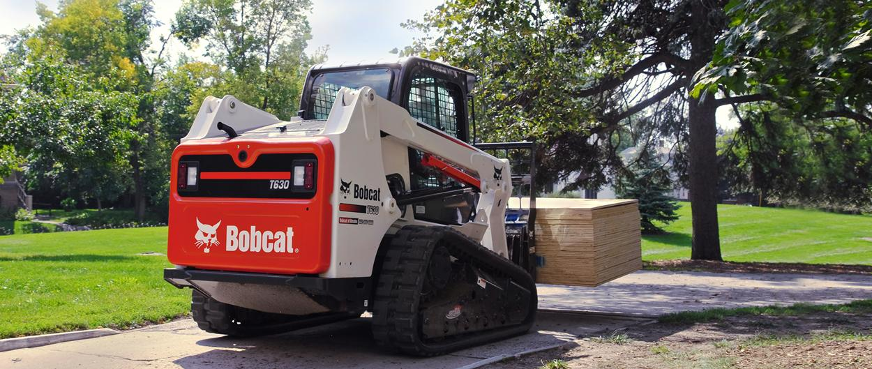 Bobcat T630 compact track loader lifts pallet.