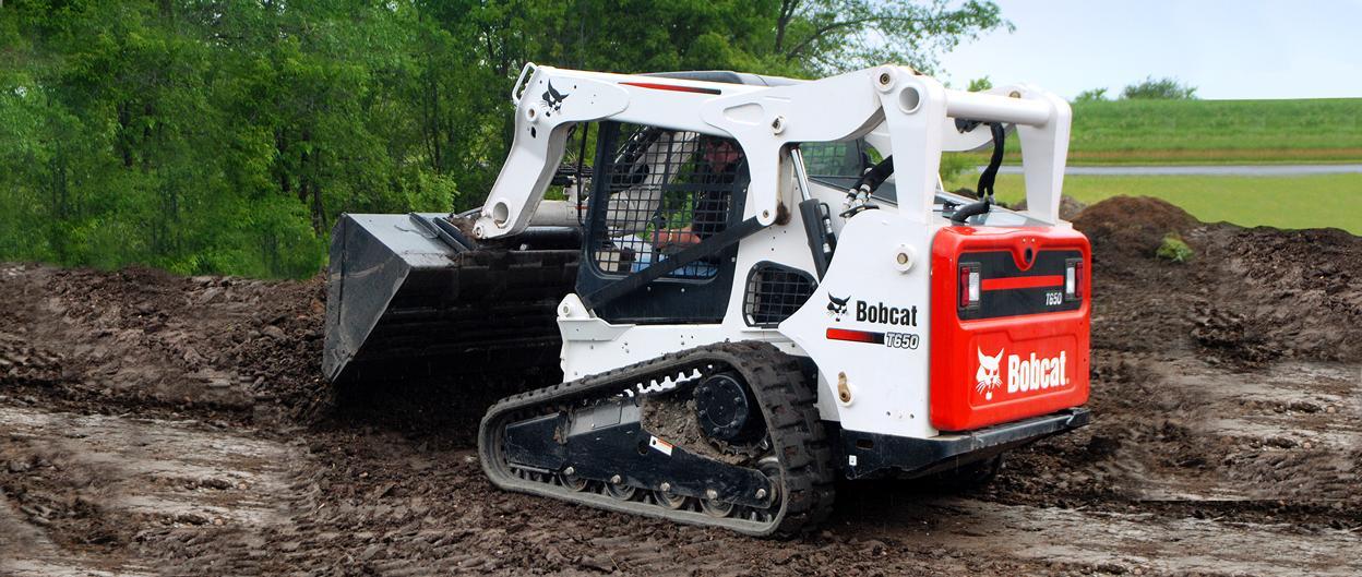 Bobcat T650 compact track loader dumps a load of black dirt.