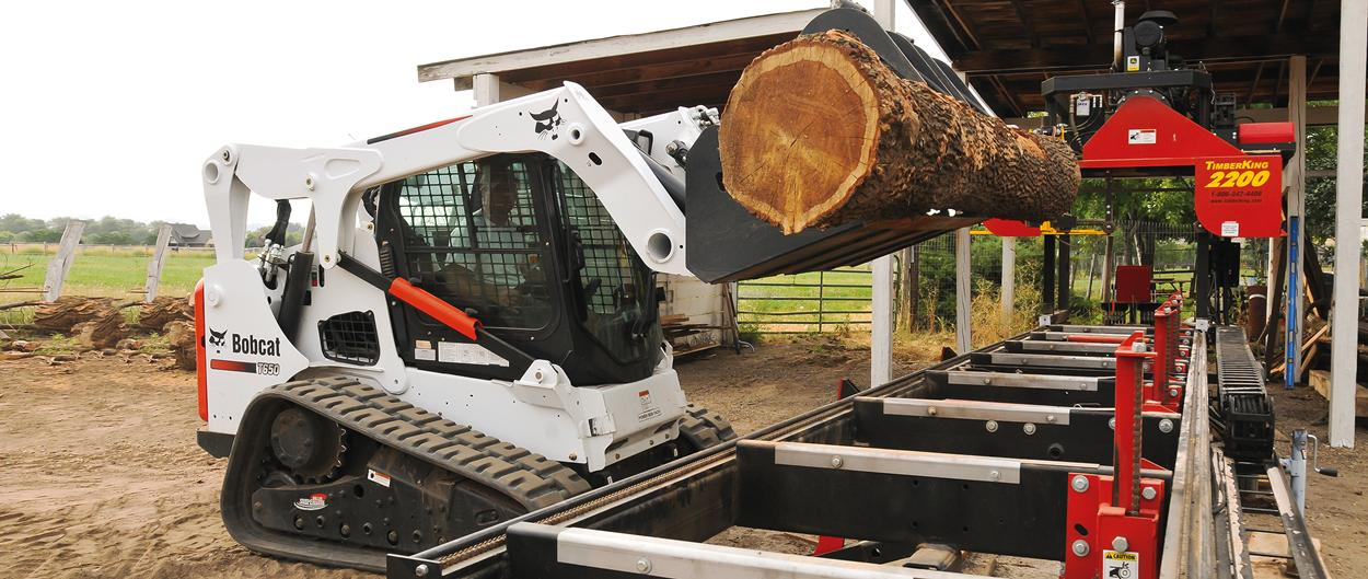 Bobcat T650 compact track loader lifts a large log.