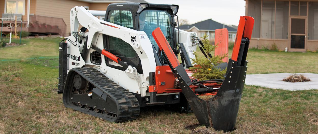 Bobcat T650 compact track loader plants a pine tree with tree spade attachment.