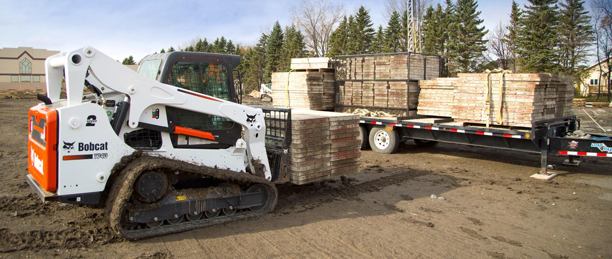 A Bobcat T740 compact track loader unloads a heavy pallet of building material from a truck.