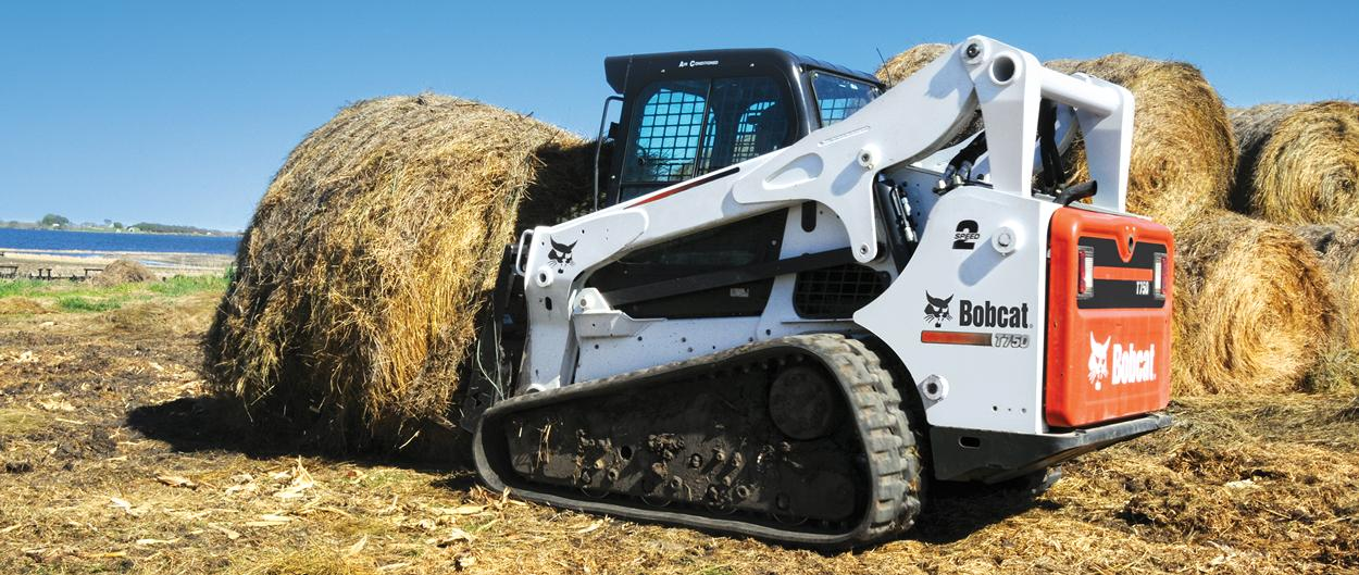 Bobcat T750 compact track loader with bale fork attachment.