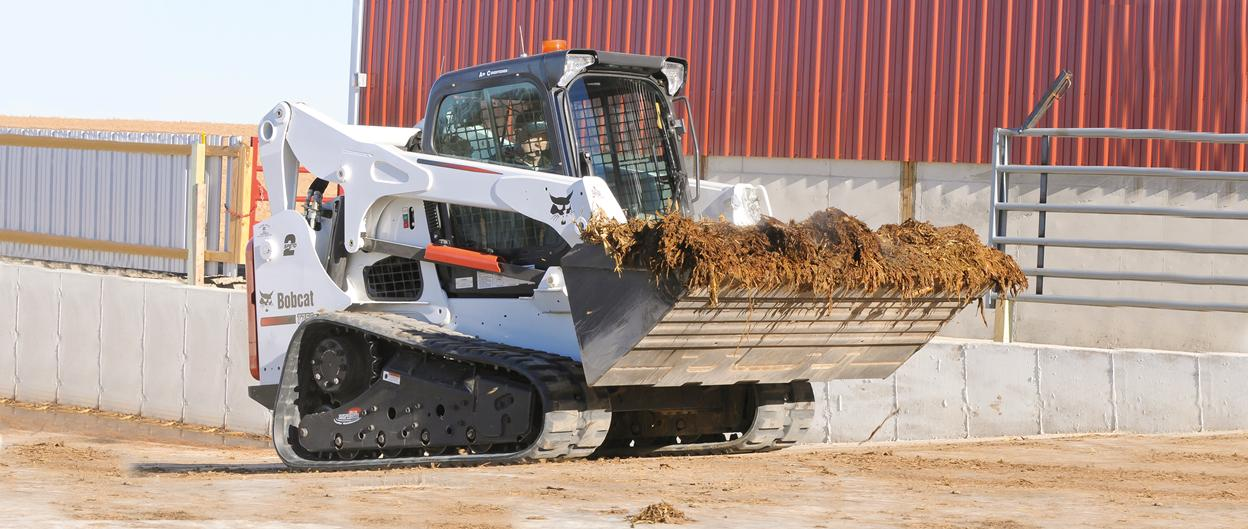 Bobcat T750 compact track loader carries bucket of manure at a farm.