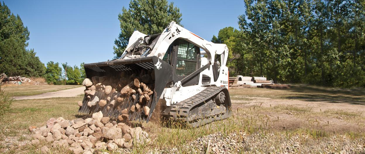 Bobcat T750 compact track loader dumps rocks into a pile.