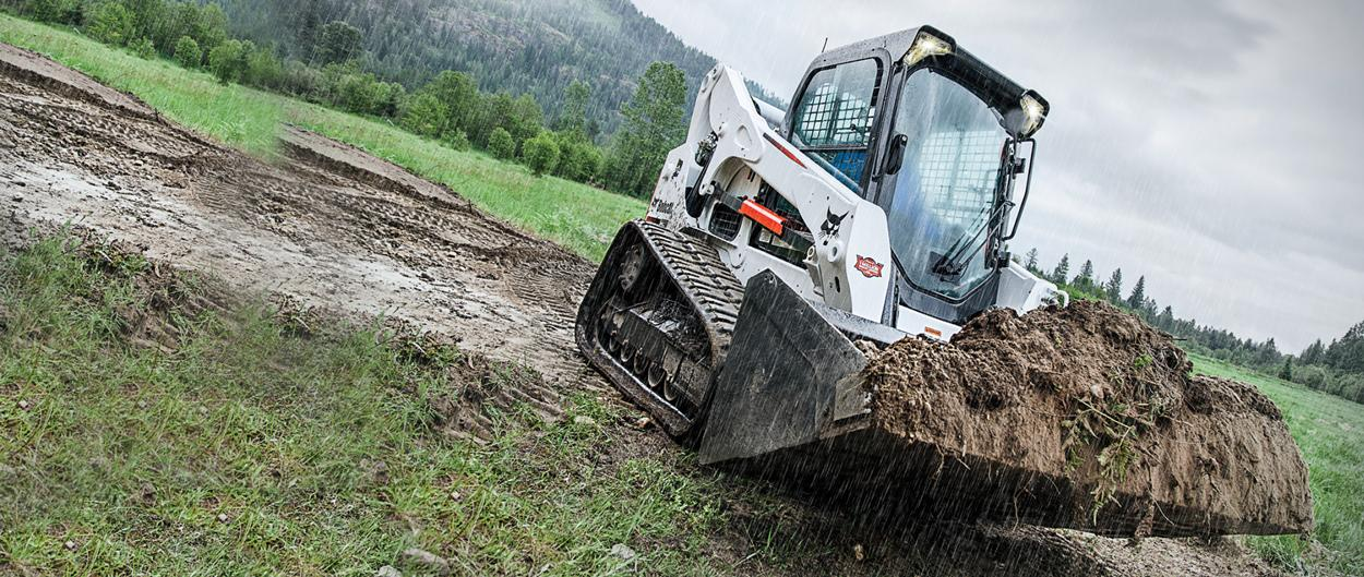A Bobcat compact track loader, with a heaping bucket of soil, travels through mud in an expansive private field.