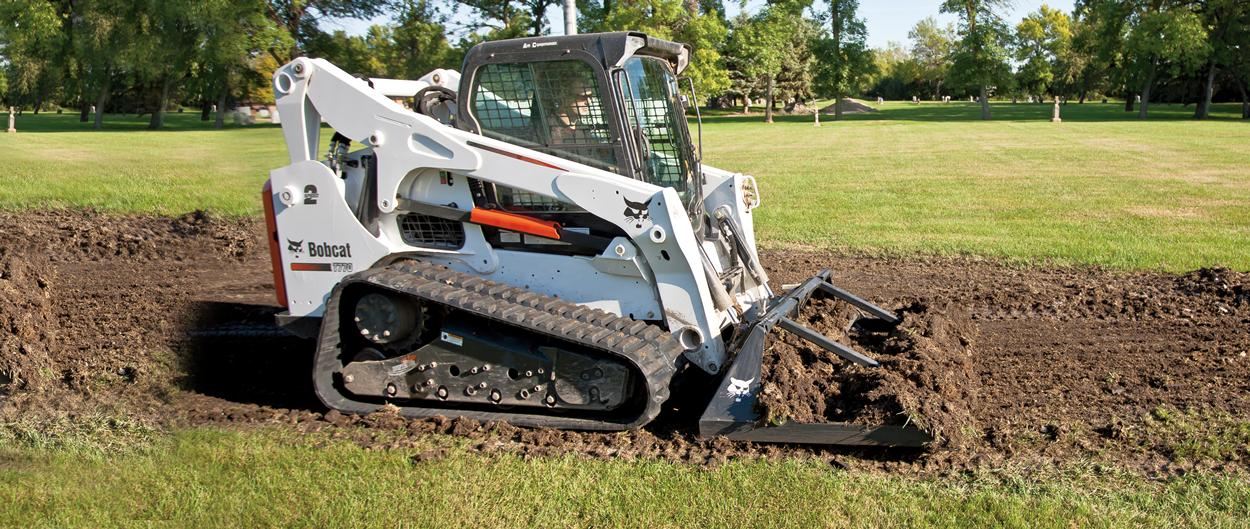 Bobcat T770 compact track loader levels dirt with landplane attachment.