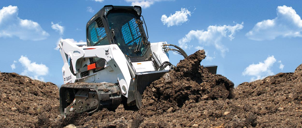 Bobcat T870 compact track loader pushes dirt on an incline.