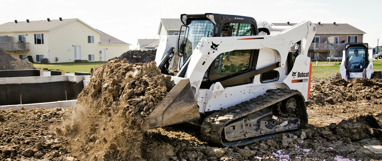 Bobcat T450 compact track loader carries a bucket of mulch in a residential backyard.