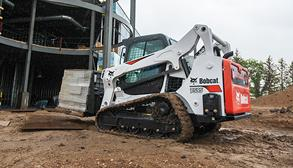 Bobcat T595 compact track loader with pallet forks moving across a job site.