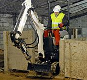 Bobcat 418 compact excavator (mini excavator) moving through a tight doorway inside a building.