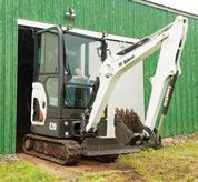 Bobcat compact excavator (mini excavator) travels through narrow barn door.