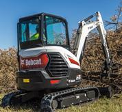 Bobcat E35 compact (mini) excavator using a grapple attachment to lift wood debris.