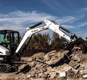 Bobcat compact (mini) excavator and grapple attachment sorting large debris on a dirt pile.