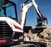 Bobcat E35 compact (mini) excavator and grapple attachment moving concrete debris.