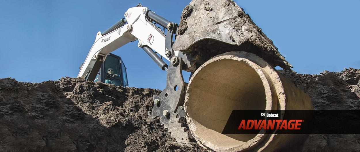 Bobcat E42 compact (mini) excavator using the exclusive Pro Clamp attachment to move a cement culvert.