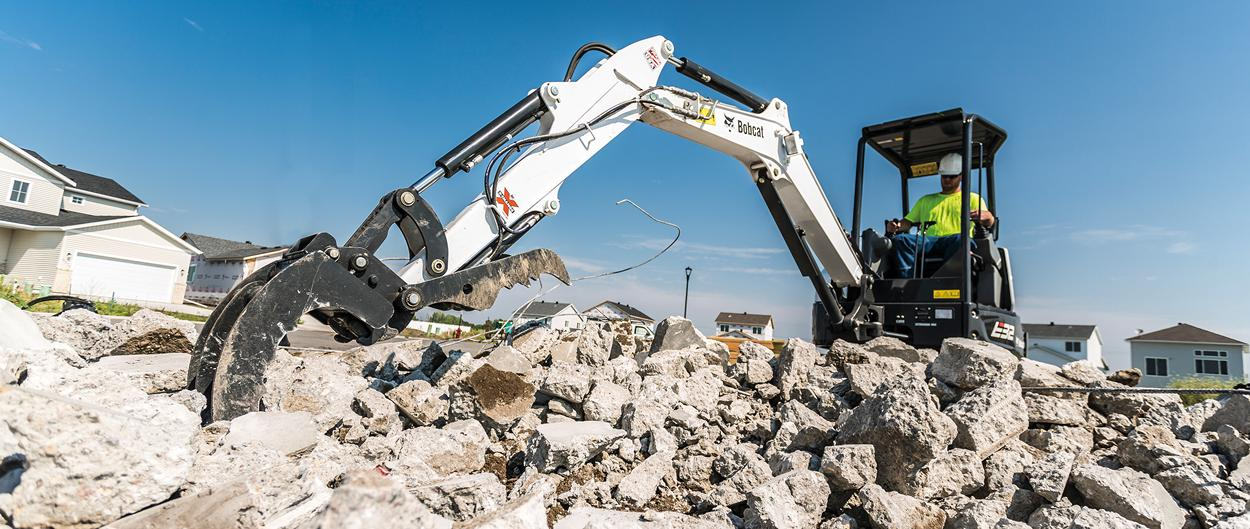 Bobcat R-Series E32 compact (mini) excavator with three-tine grapple attachment.