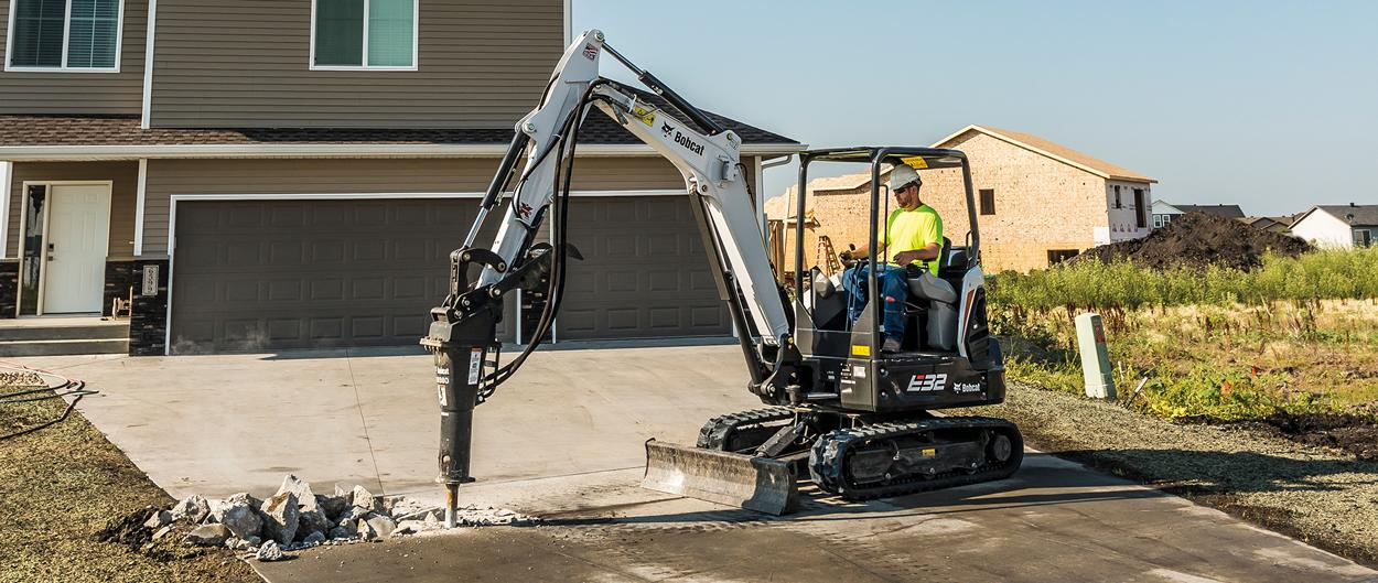 Bobcat R-Series E32 compact (mini) excavator with breaker attachment breaking up concrete driveway