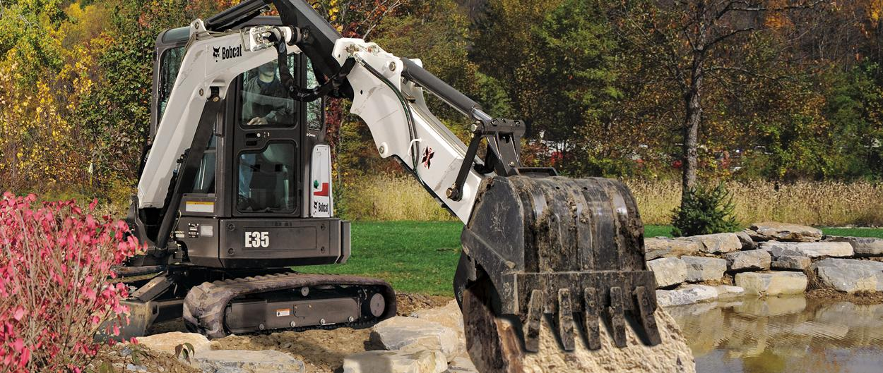 Bobcat E35 compact (mini) excavator with extendable arm lifts a rock into place while landscaping at a pond.