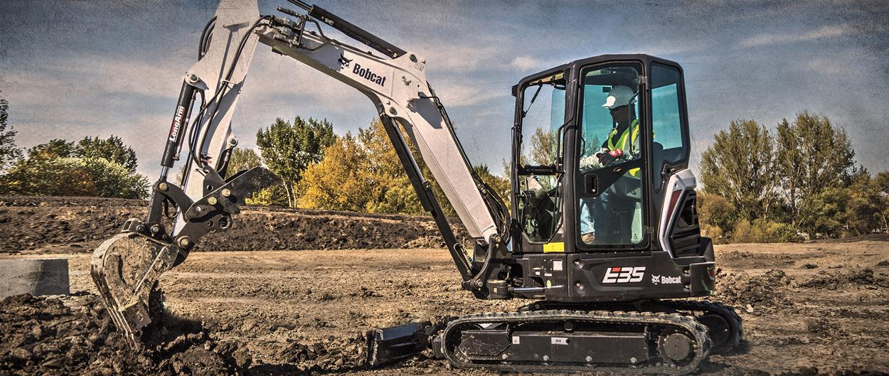 Bobcat E35 R-Series compact (mini) excavator and bucket attachment digging in a field.