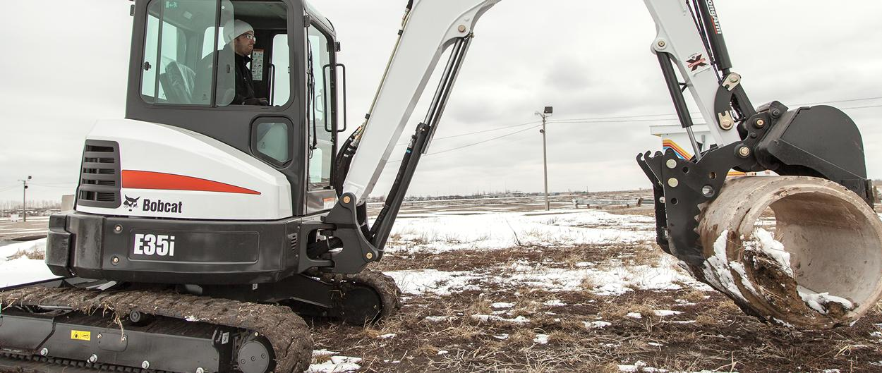 Bobcat E35i and pro clamp attachment moves a concrete pipe.
