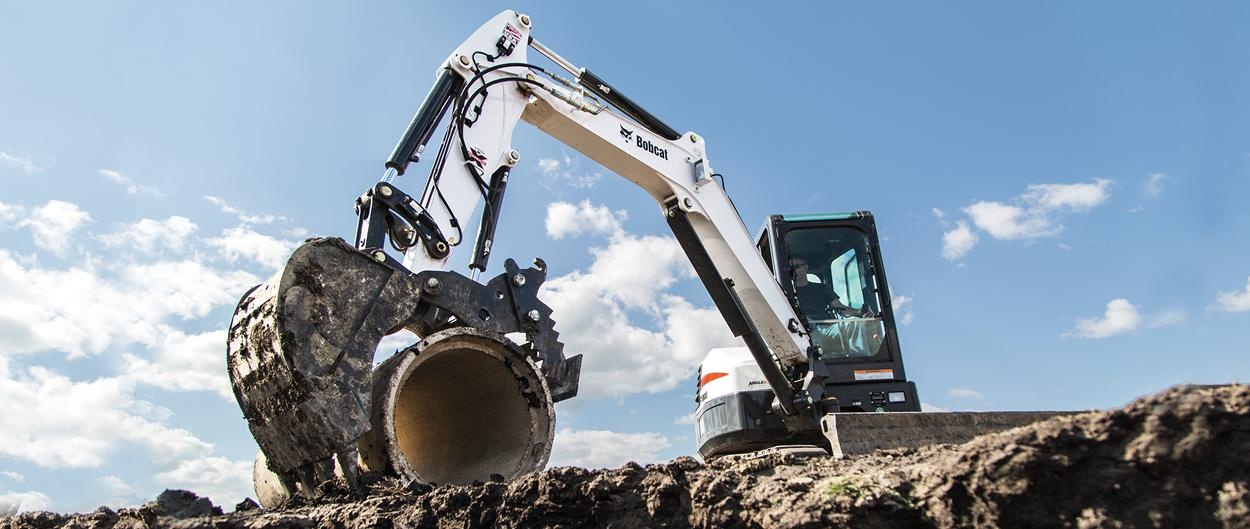 Bobcat compact (mini) excavator with pro clamp attachment lifts a concrete culvert into a trench.