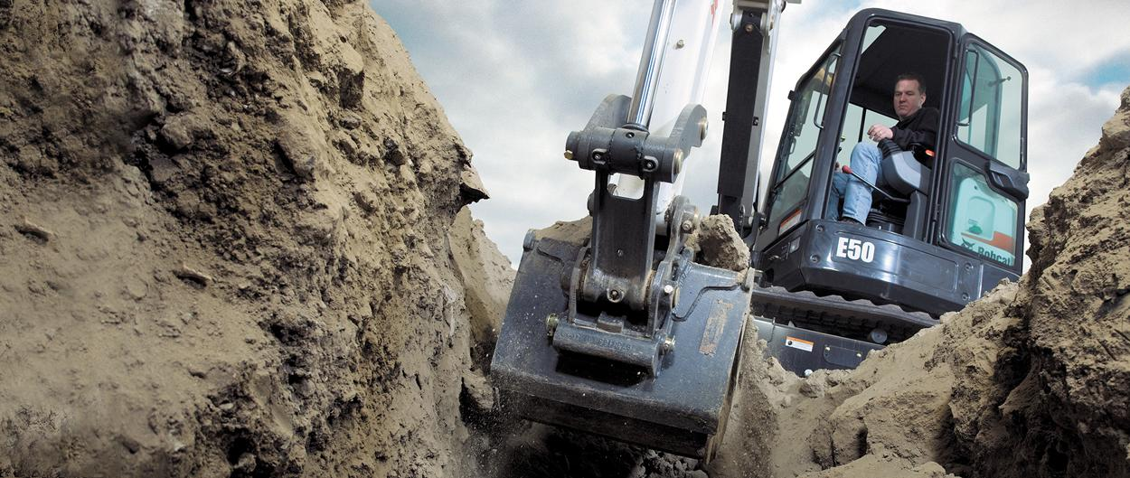Bobcat compact excavator (mini excavator) digs in trench.