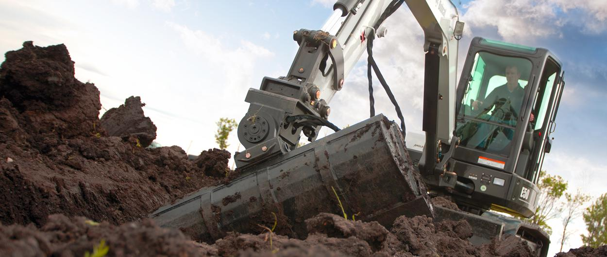 A Bobcat compact excavator digs with a grading bucket and PowerTilt swing accessory.