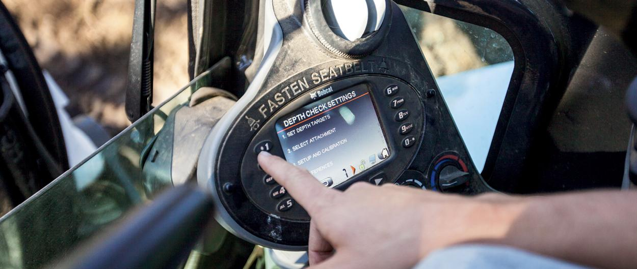 A close-up view of the deluxe instrumentation panel, with the depth check setting screen on display, in a Bobcat excavator.