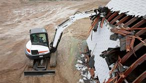 Bobcat compact (mini) excavator demolishes a roof with a bucket attachment.