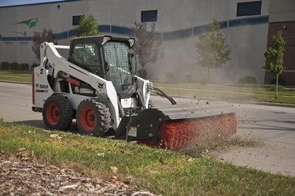 Angle broom attachment on Bobcat S570 skid-steer loader is used to sweep on a street.
