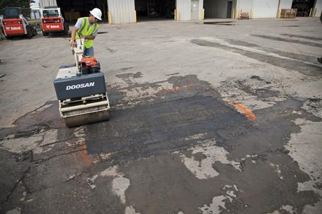 Worker uses a walk-behind vibratory compact roller to roll the repaired asphalt patch.